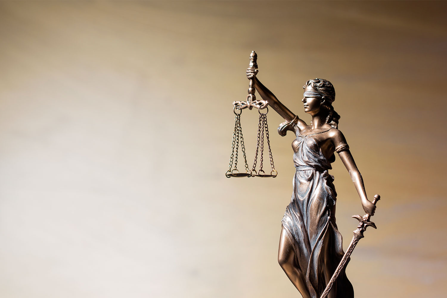 statue of lady justice holding scales of justice and sword against brown background