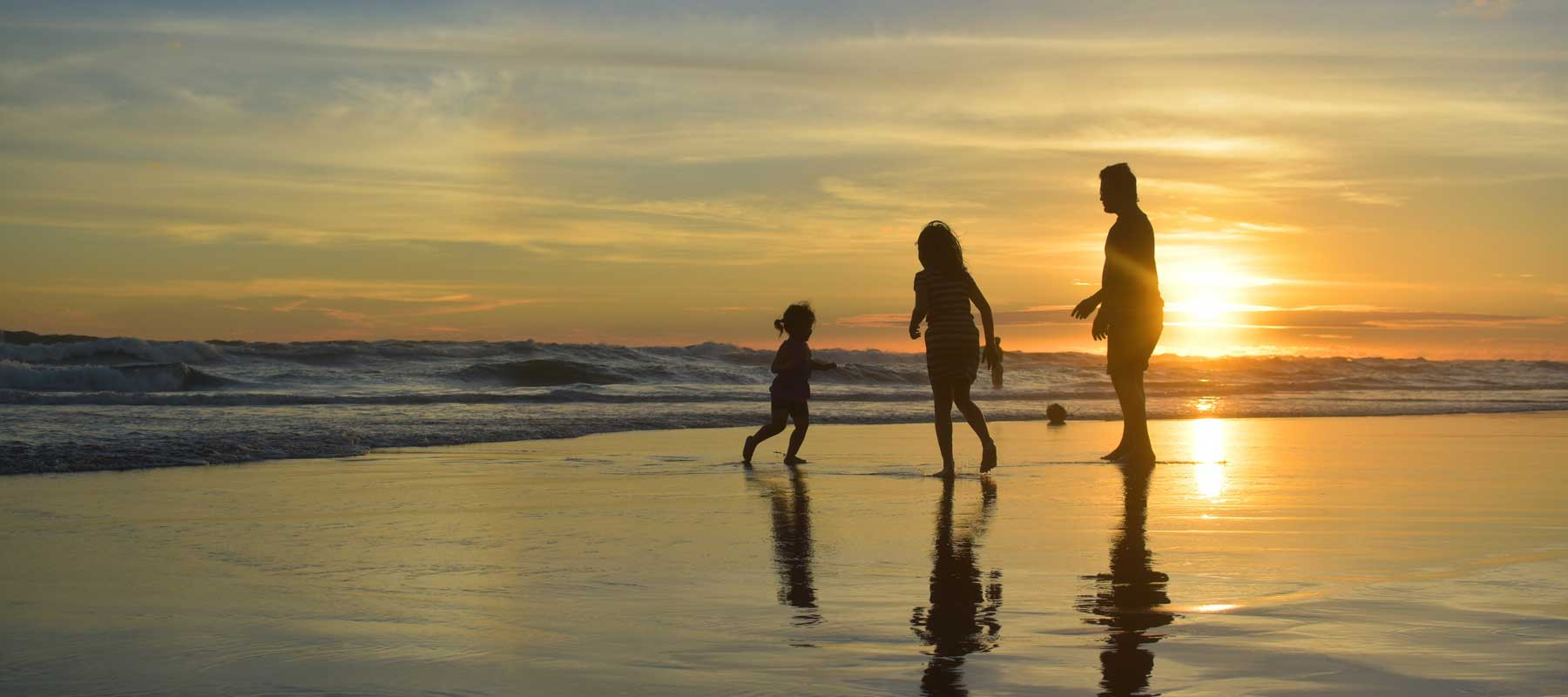 silhouetted family playing on beach at sunset