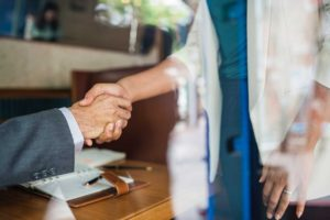 shot through glass of businessman and woman shaking hands in an office