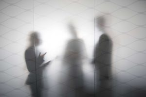 silhouette of three people talking behind frosted glass
